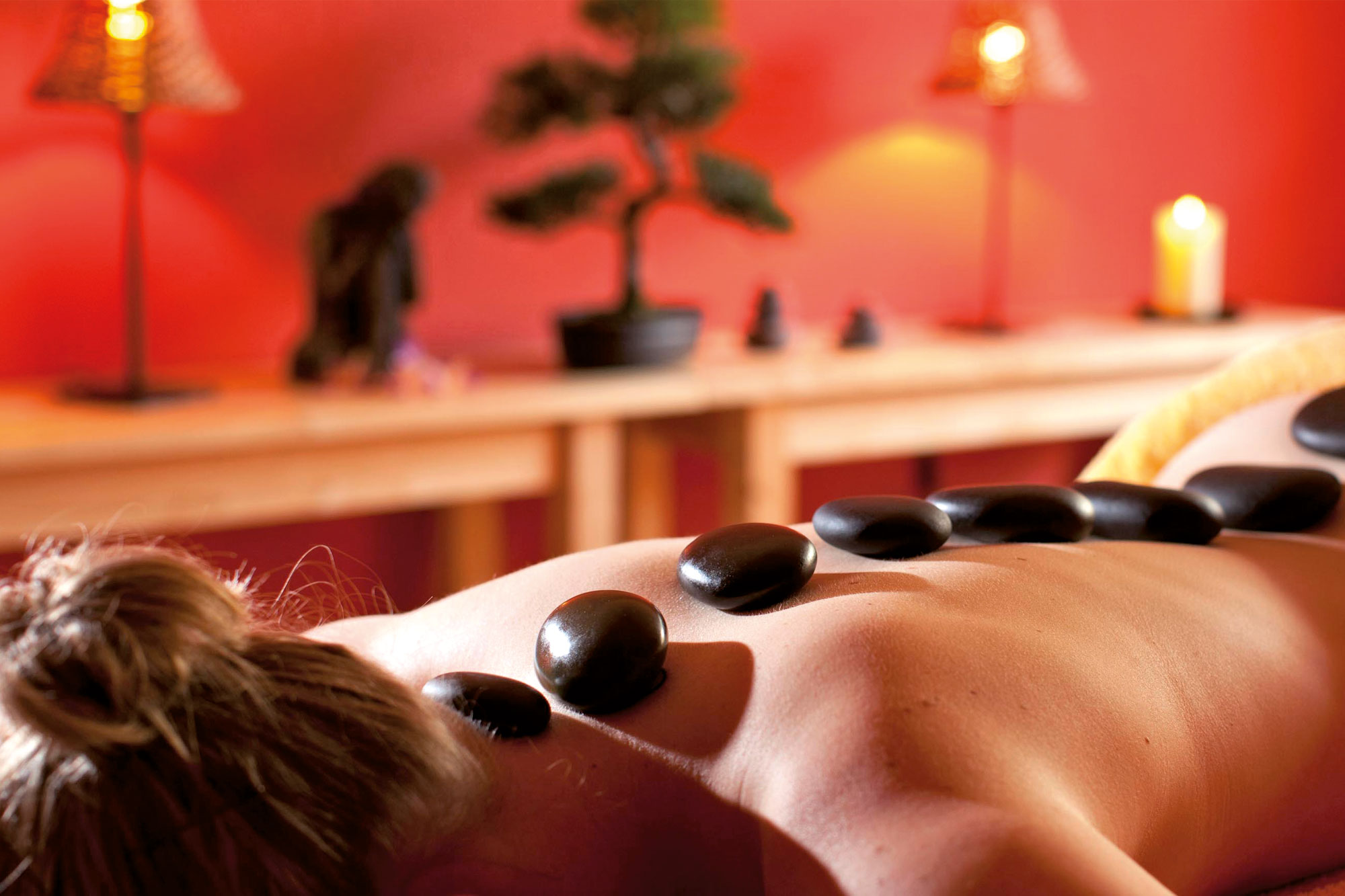 Woman during a hot stone massage at the selfness hotel Schwarzwald Panorama