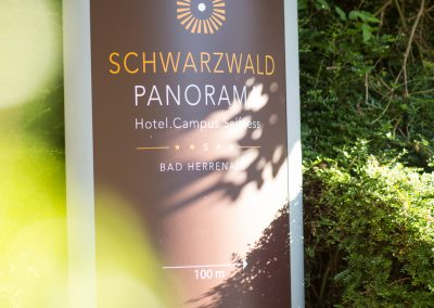 """A billboard with text on it pointing towards the entrance of the hotel SCHWARZWALD PANORAMA. Text: """"SCHWARZWALD PANORAMA – Hotel. Campus. Selfness. Bad Herrenalb – 100m -->"""""""