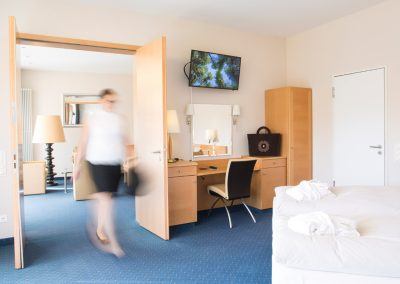 A person walking through a spacious suite of the hotel SCHWARZWALD PANORAMA