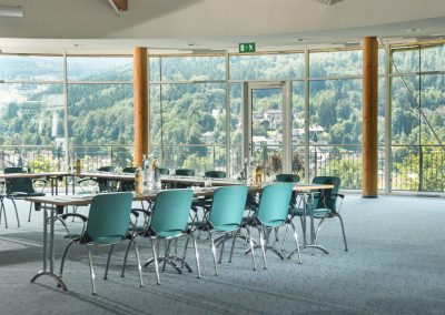 A conference room with turqoise carpet and chairs located just behind a stunning panorama view of the black forest, as a part of the conference facilities of the conference hotel SCHWARZWALD PANORAMA