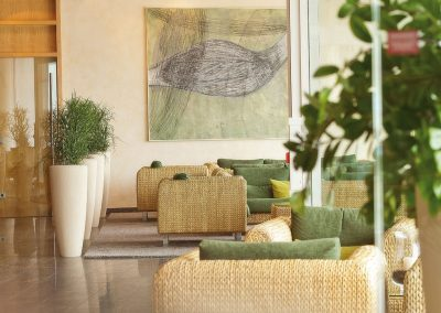 A lounge are with multiple couches, plants and a large painting on the wall, at the wellnesshotel SCHWARZWALD PANORAMA