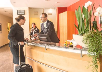 A businesswoman in front of the receptionist desk, being consulted by the staff of the hotel SCHWARZWALD PANORAMA