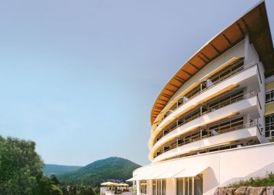 The exterior of the wellness hotel SCHWARZWALD PANORAMA right next to the green woods of the black forrest, all underneath a clear blue sky.