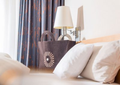 A decorative brown bag with the SCHWARZWALD PANORAMA logo on it is located next to a bed with white linen.