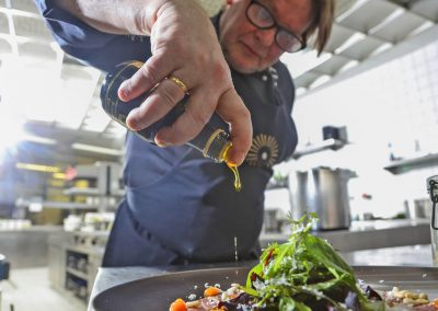 Chef in the Black Forest Panorama drizzled a ready-made salad with high-quality oil