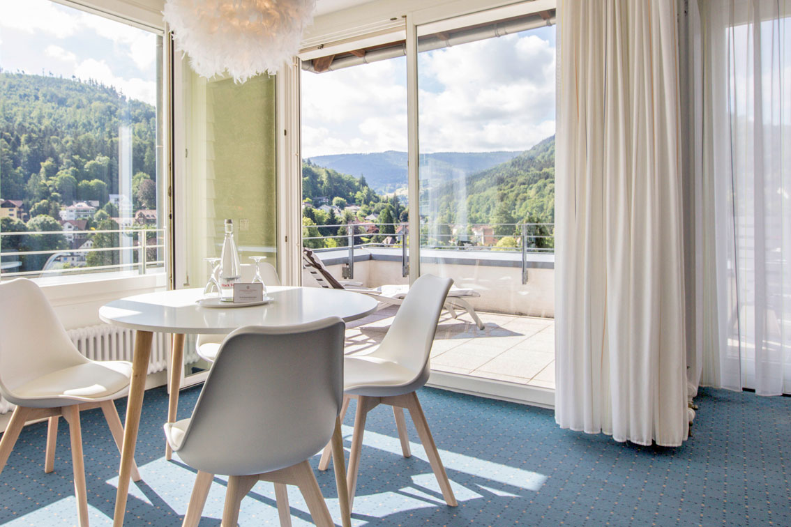 Dining area with table with four chairs in an apartment in the hotel Schwarzwald Panorama and adjoining terrace with sun loungers