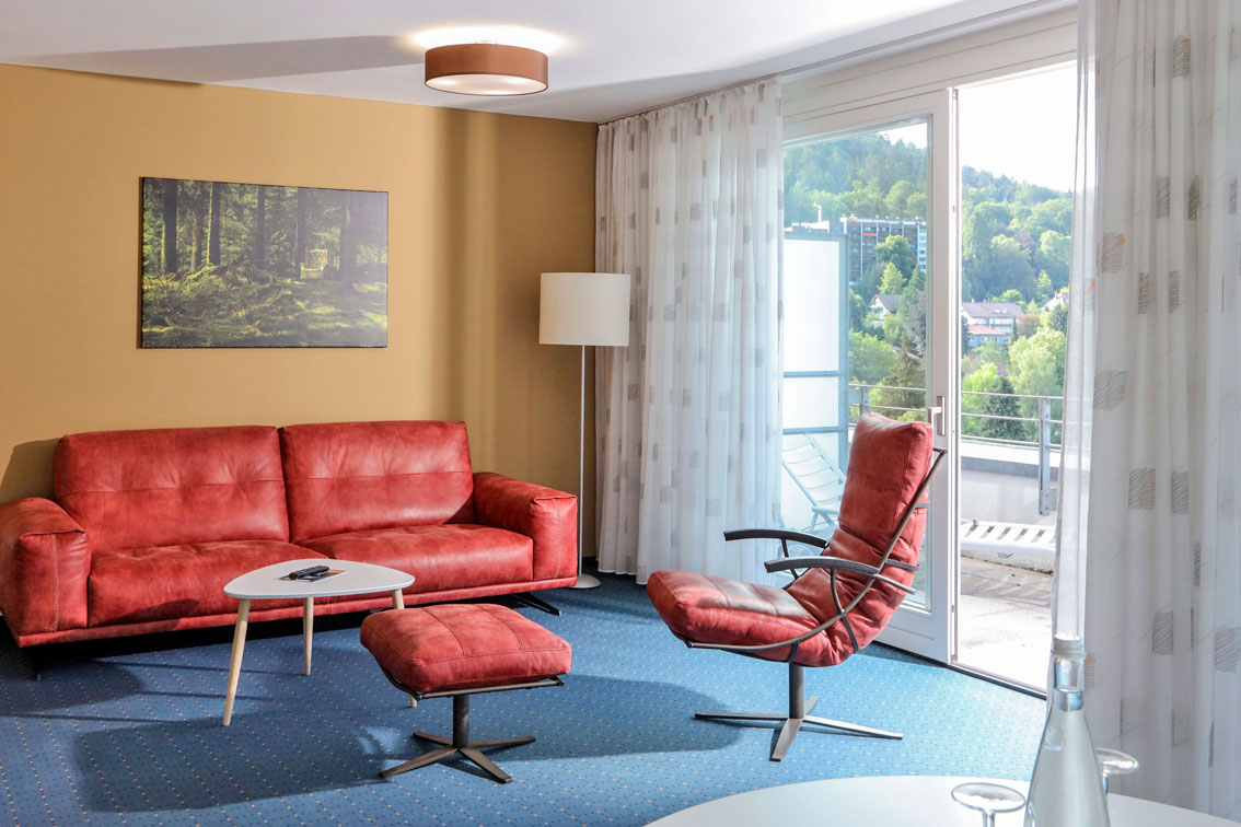Bright apartment in the Hotel Schwarzwald Panorama with comfortable couch and armchair and balcony