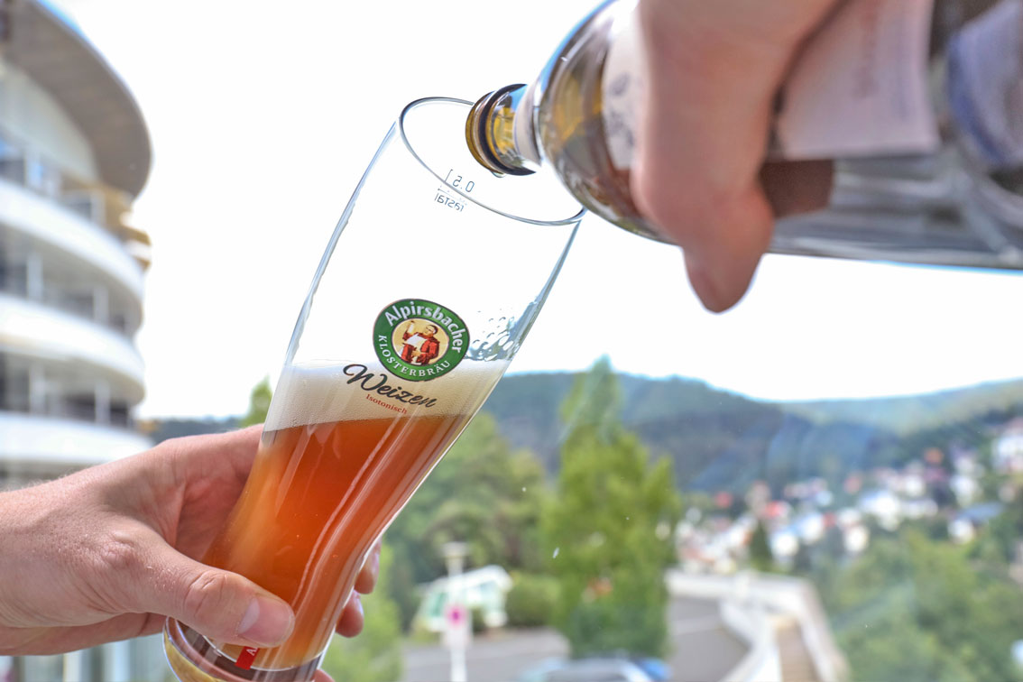 Man pours a glass of fresh wheat on the balcony of the hotel Schwarzwald Panorama and looks out over the surrounding nature