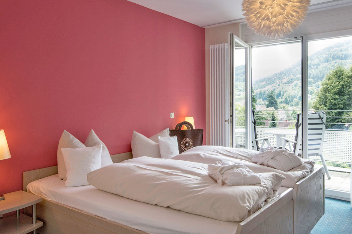 Bedroom with comfortable double bed in an apartment in the Hotel Schwarzwald Panorama with access to the balcony